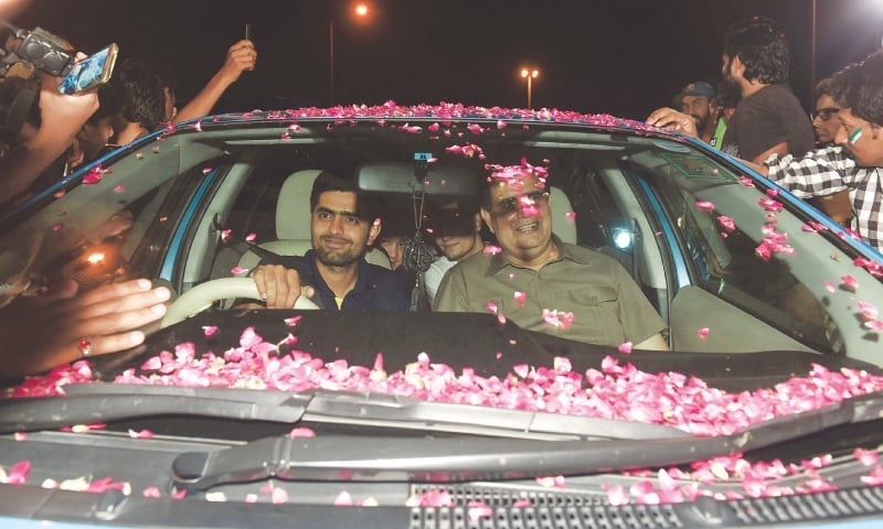 BATSMAN Babar Azam is surrounded by fans as he drives his car after arriving in Lahore.—AFP