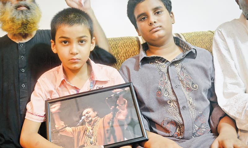 Amjad Sabri's sons Mujaddid and Aun with their father's portrait.—Fahim Siddiqi/White Star