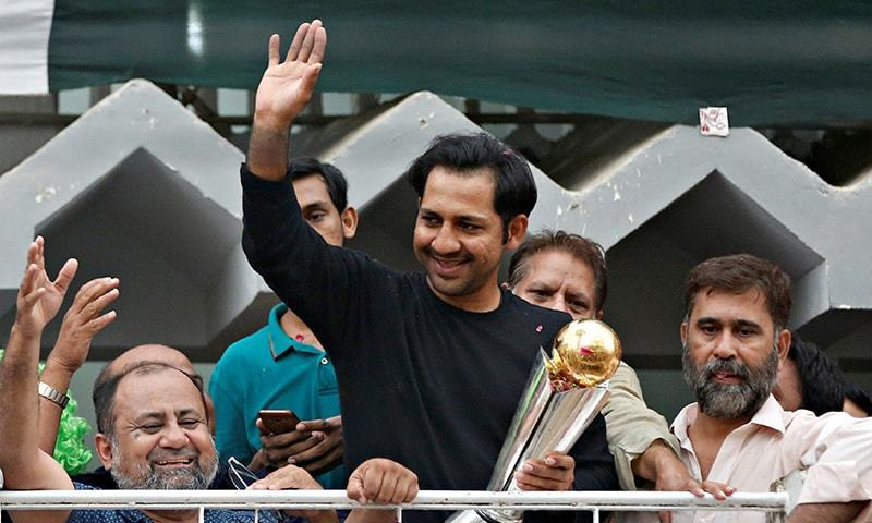 Sarfraz Ahmad gestures to cricket fans as he celebrates winning the ICC Champions Trophy upon his arrival at his house in Karachi. — Photo: Reuters.
