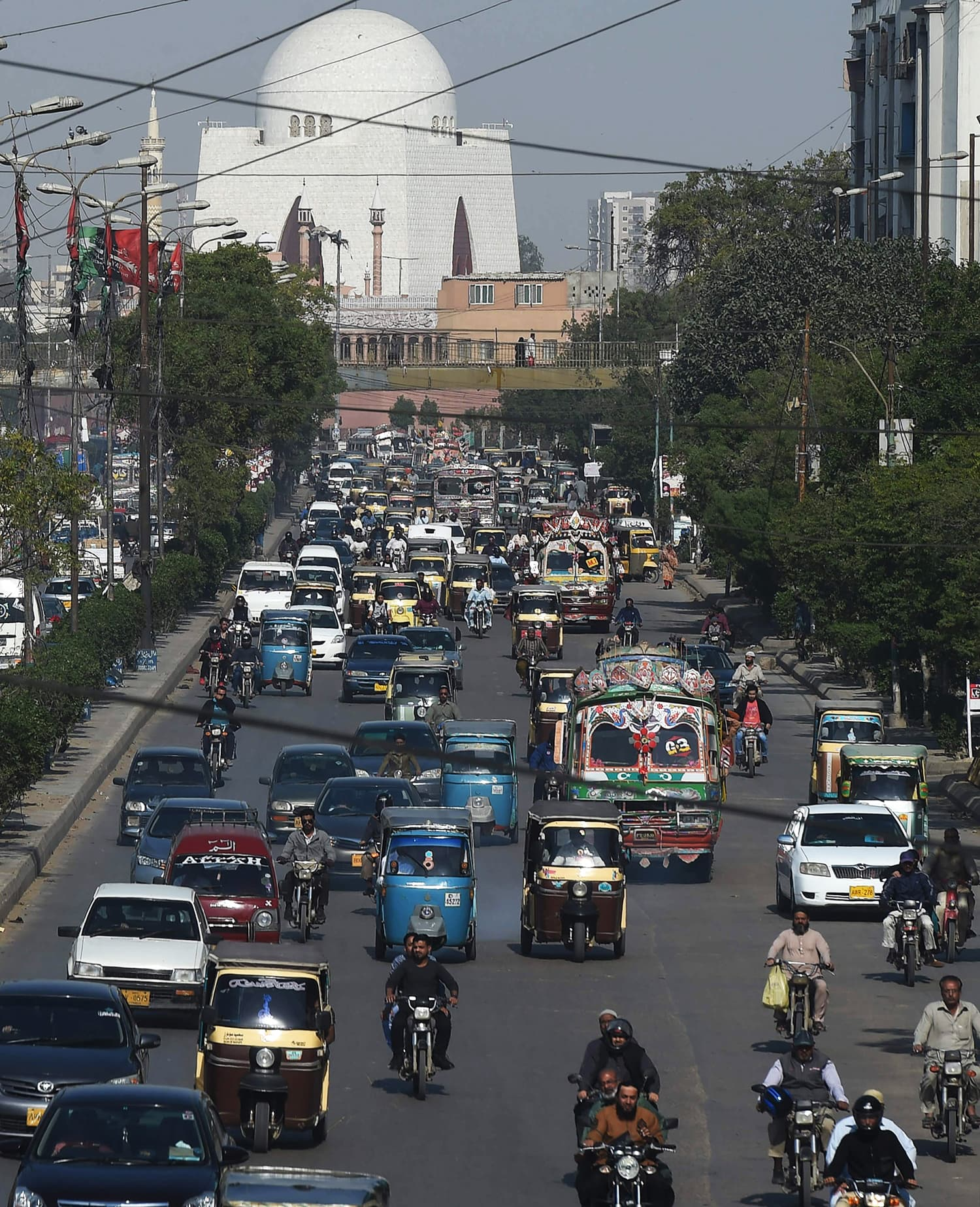 Commuters drive on a busy street in the port city of Karachi. ─ AFP.