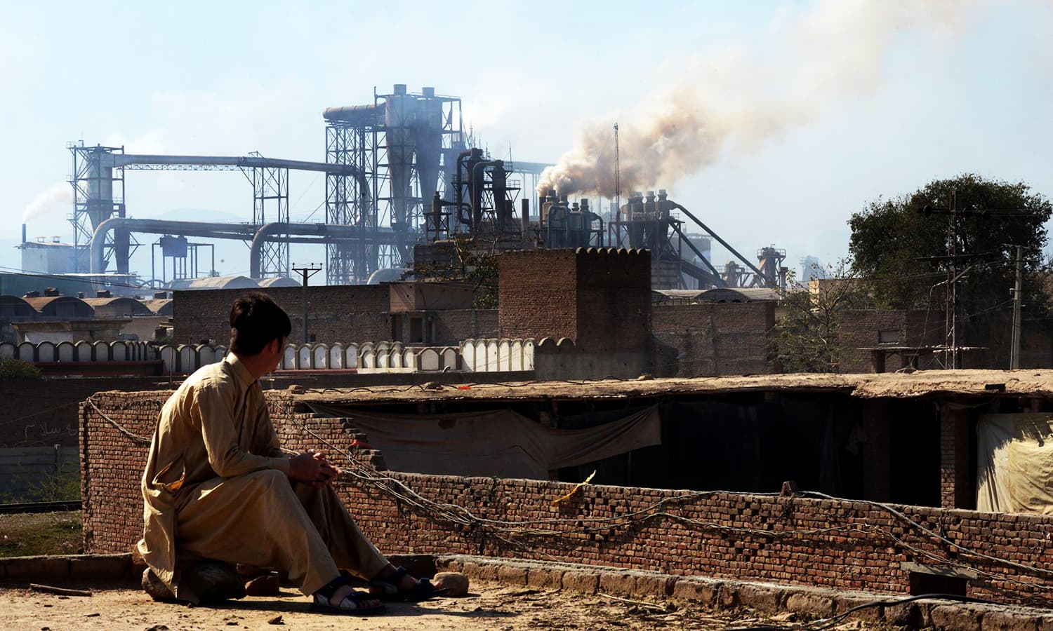 A worker watches smoke rise from factories on the outskirts of Peshawar. ─ AFP