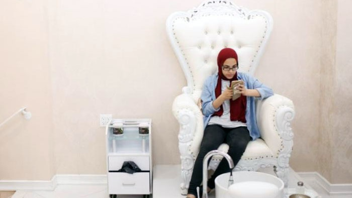 A Muslim woman uses her phone while waiting for a family member to receive treatment at the Le'Jemalik Salon and Boutique in Brooklyn, New York. ─Reuters