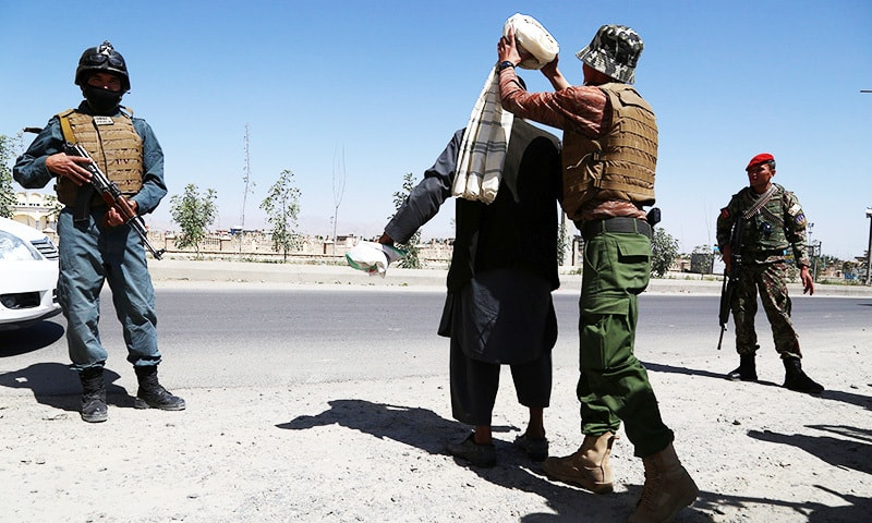 Afghan security soldiers search a man at a checkpoint, ahead of Eidul Fitr.—AFP