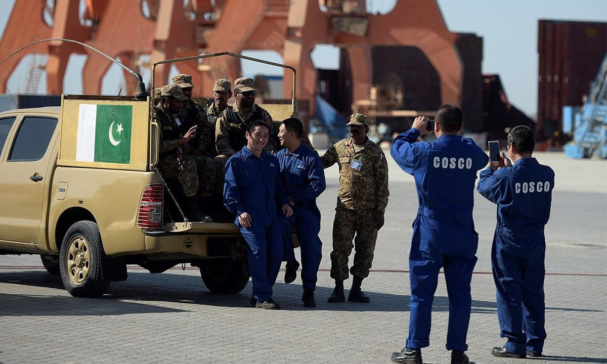 Crew members of a Chinese ship take pictures with Pakistani security officials in Gwadar. —AFP