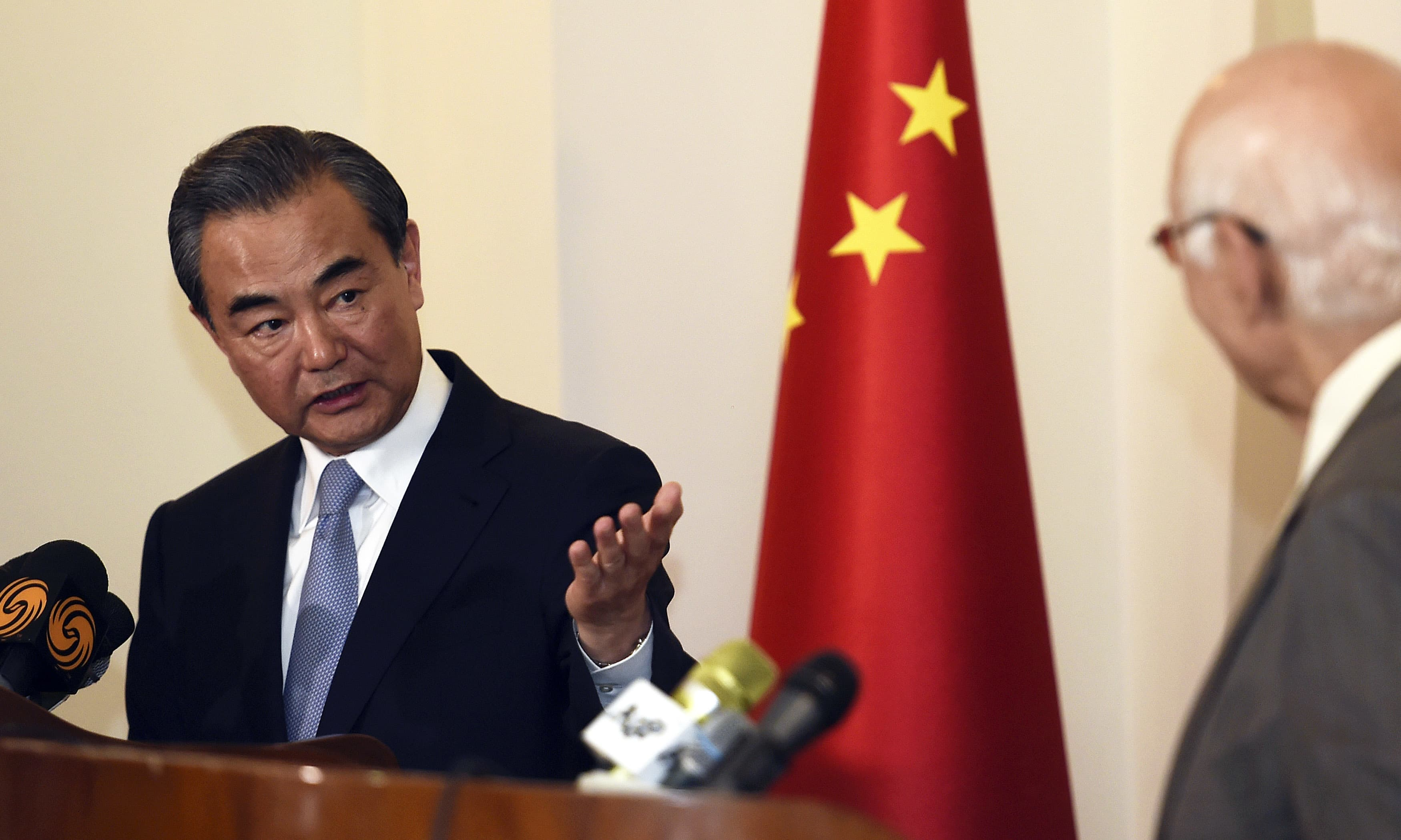Chinese Foreign Minister Wang Yi gestures to Sartaj Aziz during a press conference in Rawalpindi. —AP