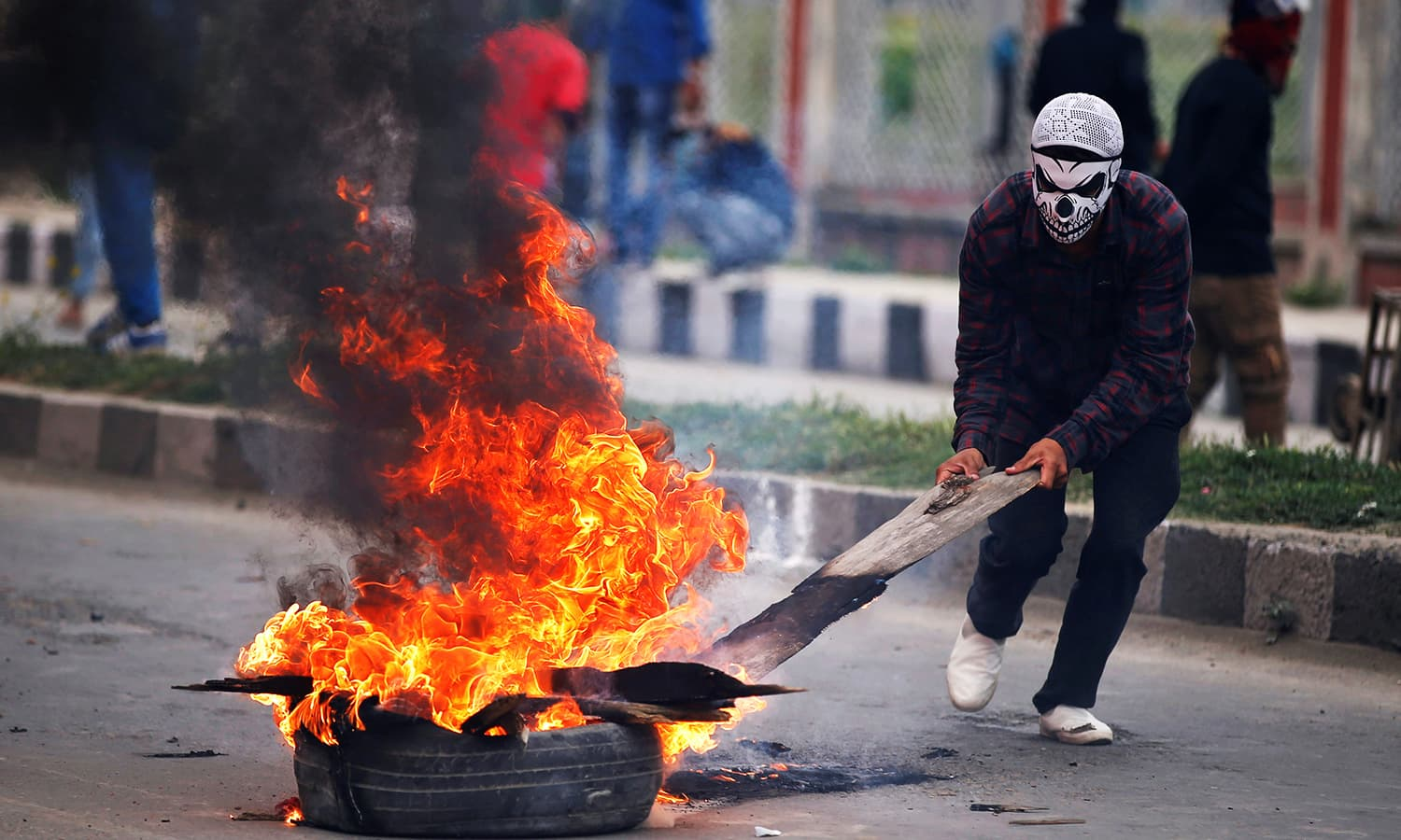 A masked demonstrator pulls a burning tyre during a protest after Eidul Fitr prayers in Srinagar. ─ Reuters