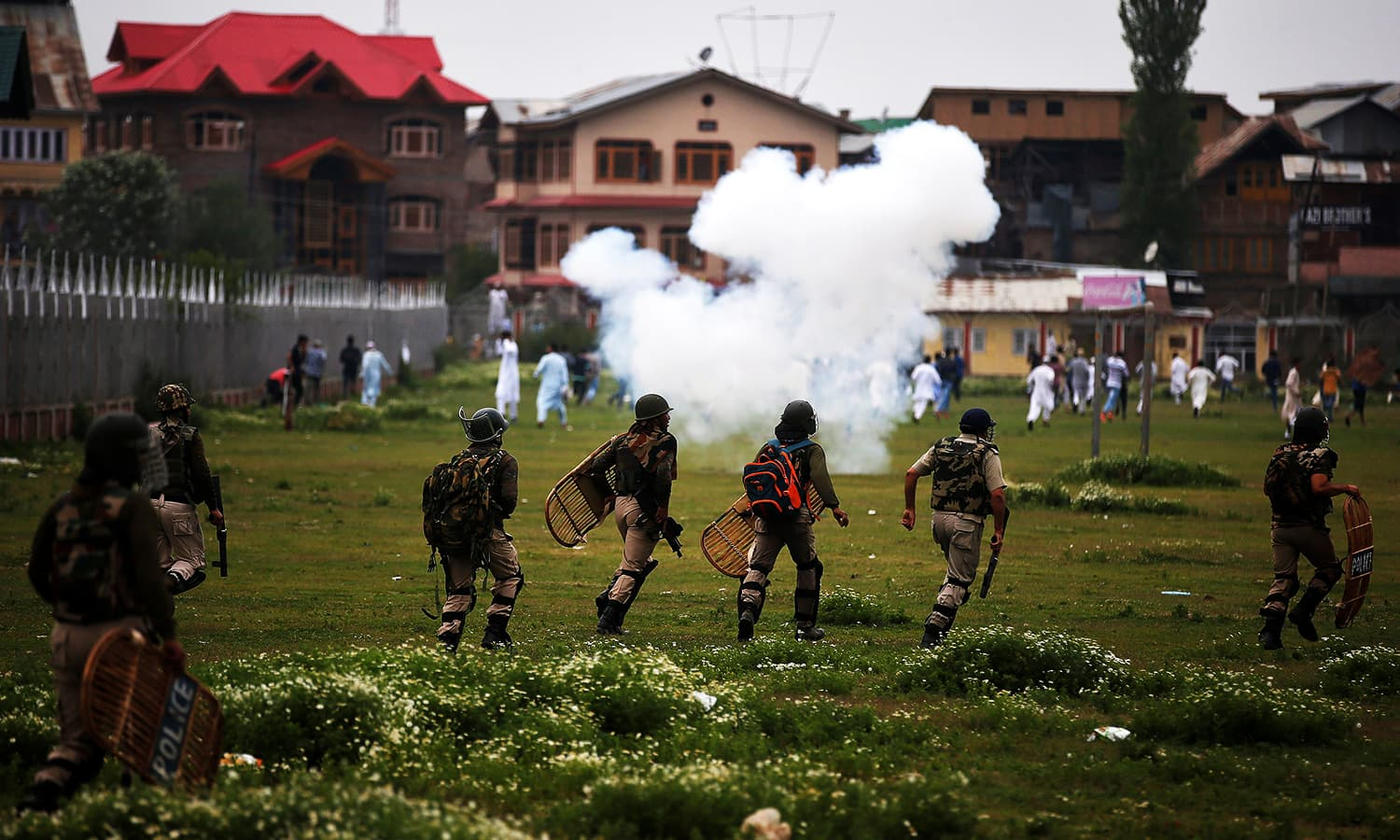 Indian police chase the demonstrators during a protest after Eidul Fitr prayers in Srinagar. ─ Reuters