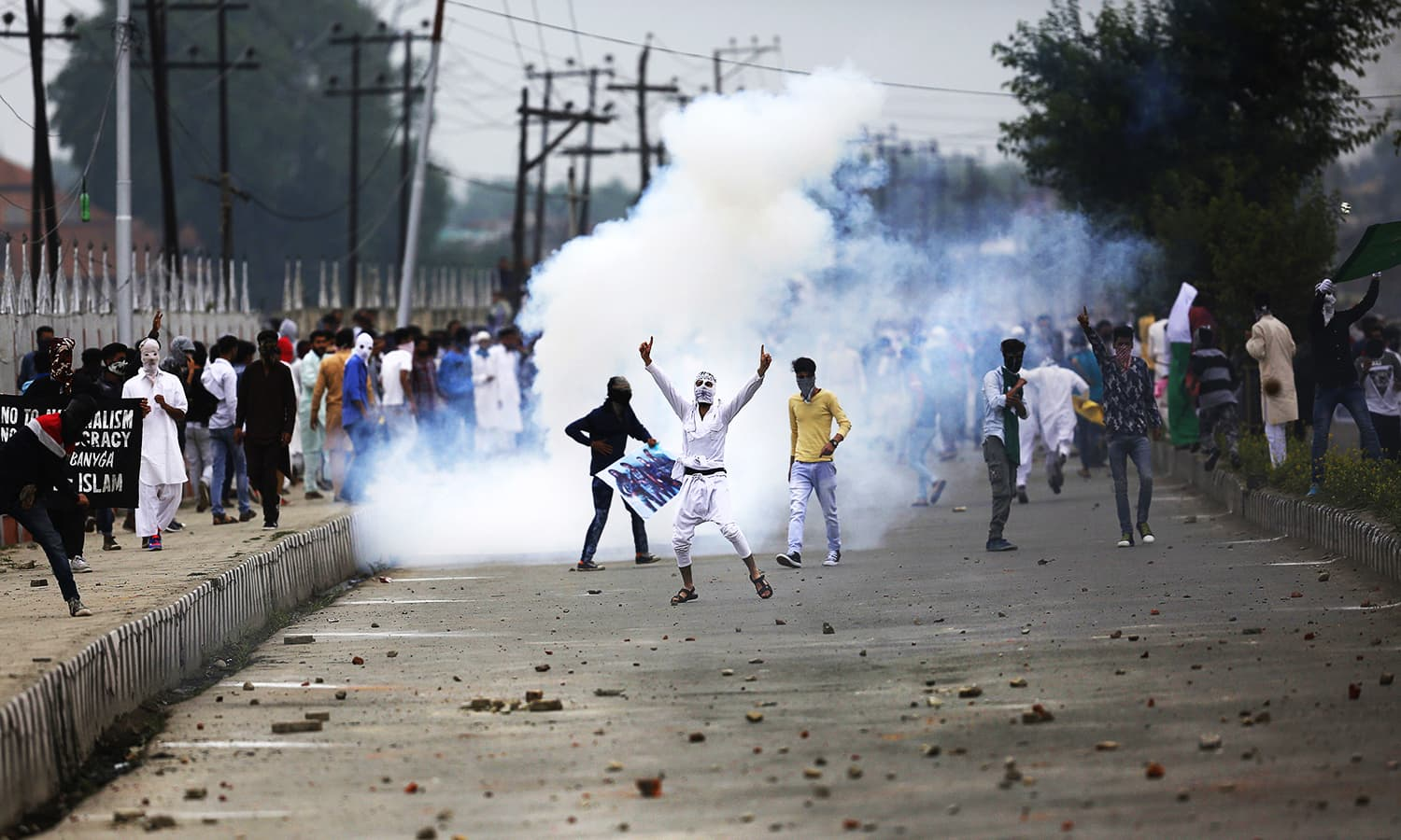 Protesters shout anti-India and pro-freedom slogans amid teargas smoke during a protest after Eidul Fitr prayers in Srinagar. ─ AP