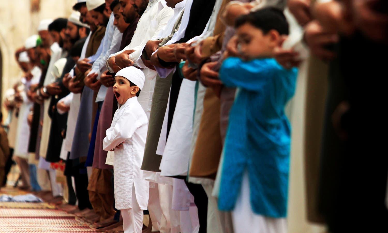 A boy yawns as he attends Eid prayers in Rawalpindi. ─ Reuters