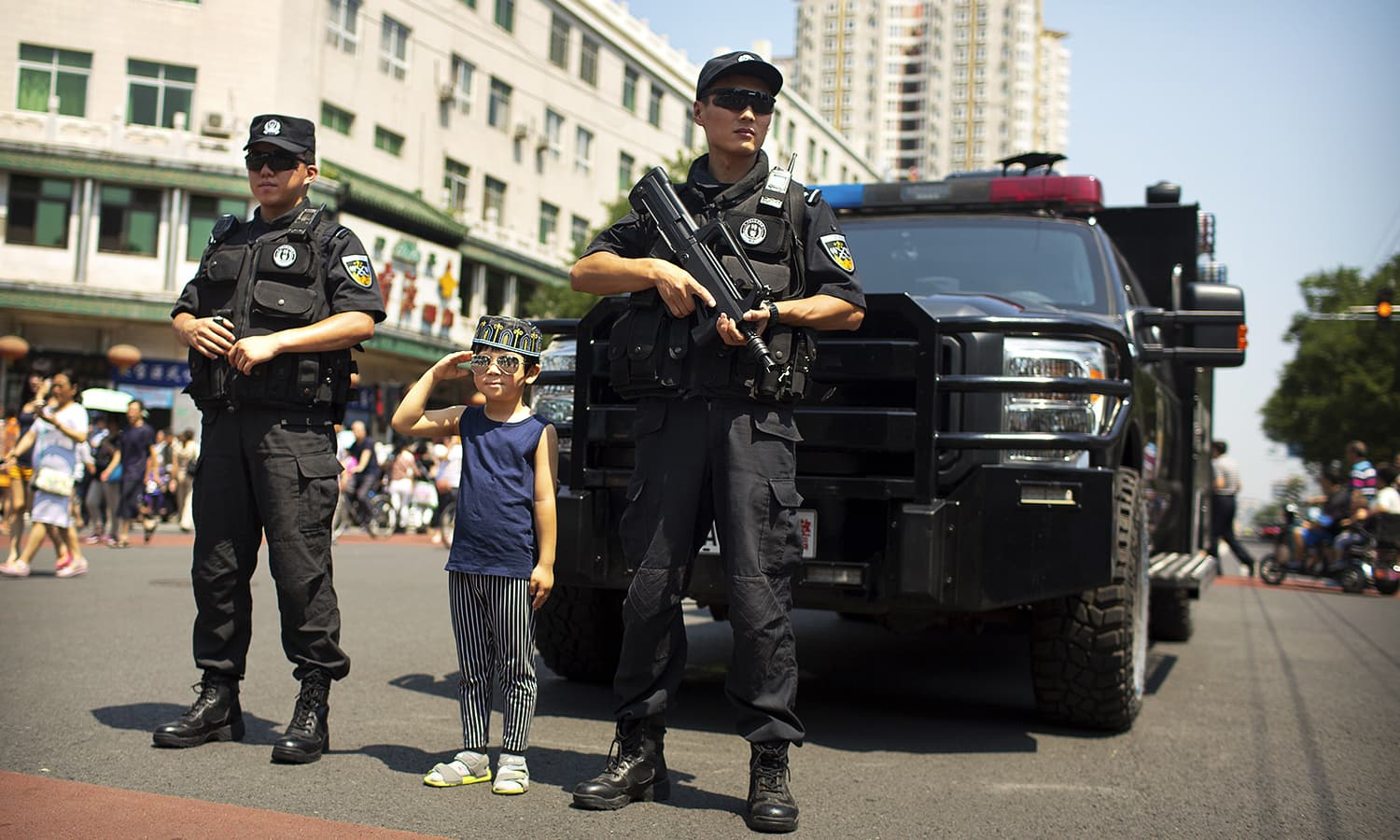 A boy wearing a prayer cap salutes as he stands with armed Chinese policemen while they guard an intersection near the Niujie Mosque after Eid prayers in Beijing. ─ AP