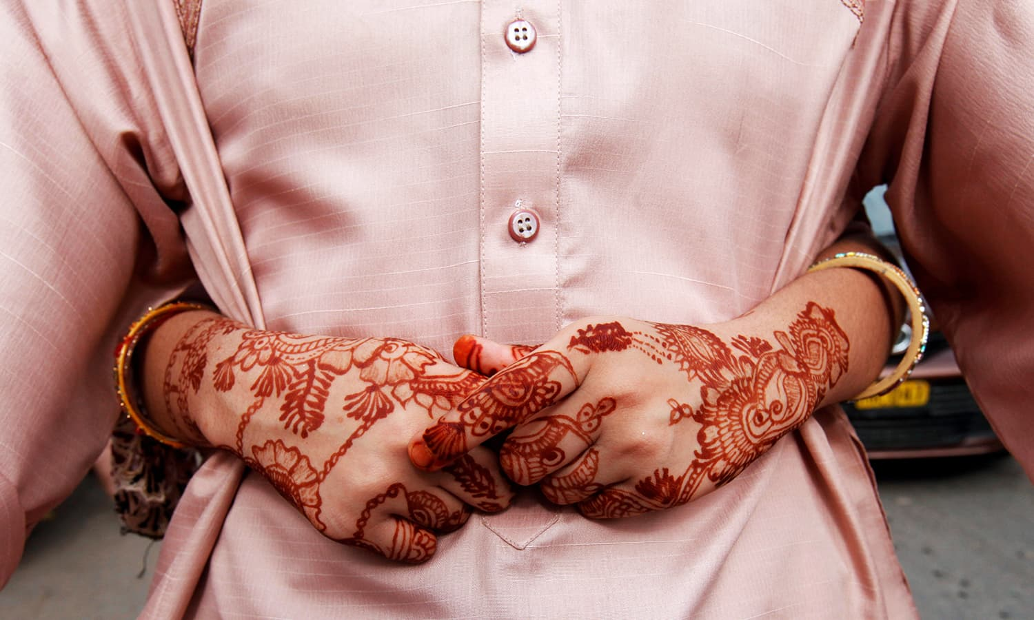 The hands of a girl, adorned with henna patterns, as she puts her arms around her father while traveling on bike during Eid in Karachi. ─ Reuters
