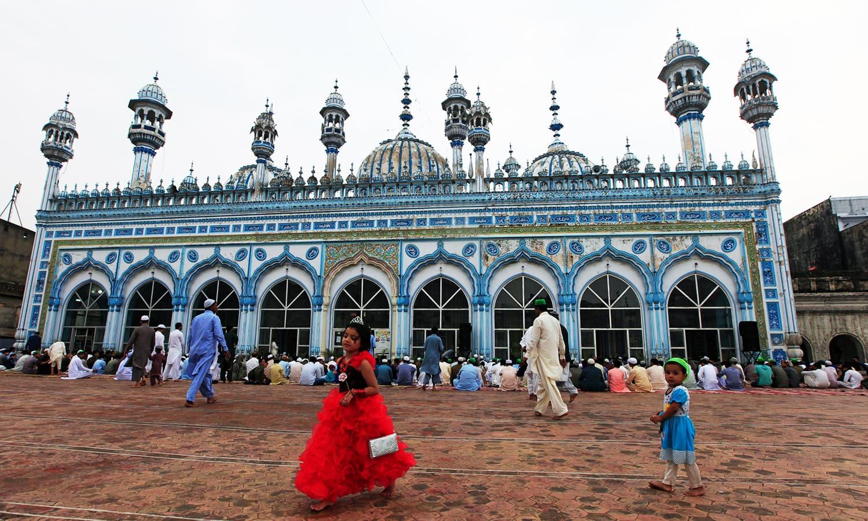 A girl walks inside a mosque before Eid prayers in Rawalpindi. ─ Reuters