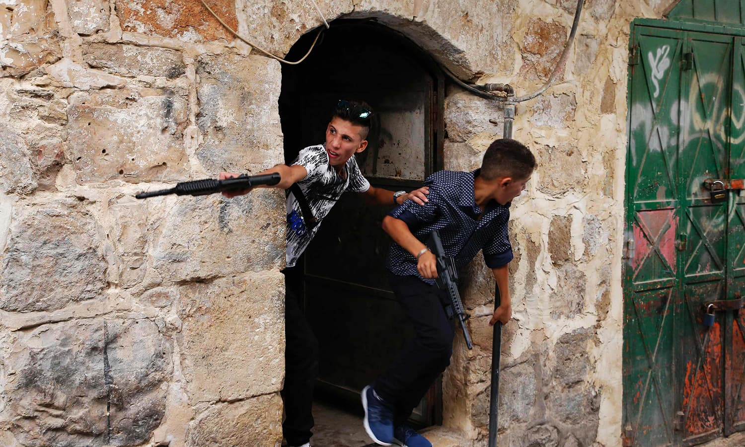 Palestinian children play with toy guns in the West Bank town of Hebron. ─ AFP