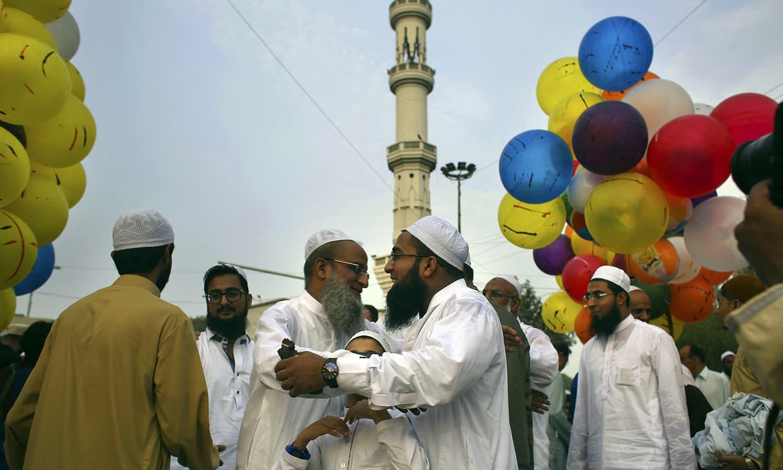 Men greet each other after the Eid prayers in Karachi. ─ AP