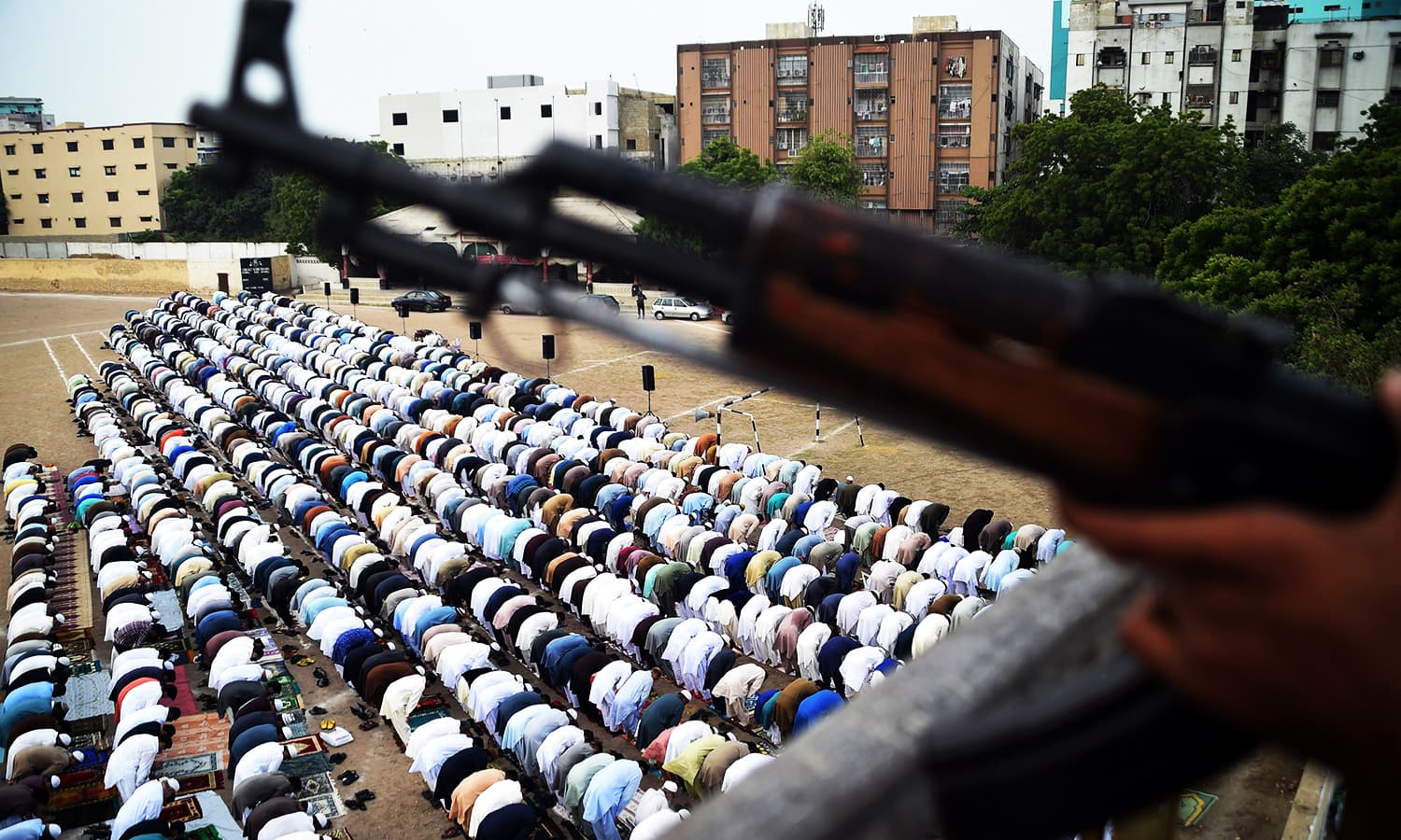 A policeman stands guard as people offer Eid prayers at an Eidgah ground in Karachi. ─ AFP