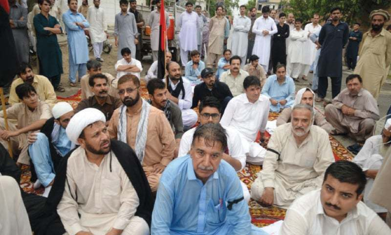 Protesters stage a sit-in on Sher Shah Suri Road, Peshawar, on Wednesday, against Peshawar blasts.─White Star