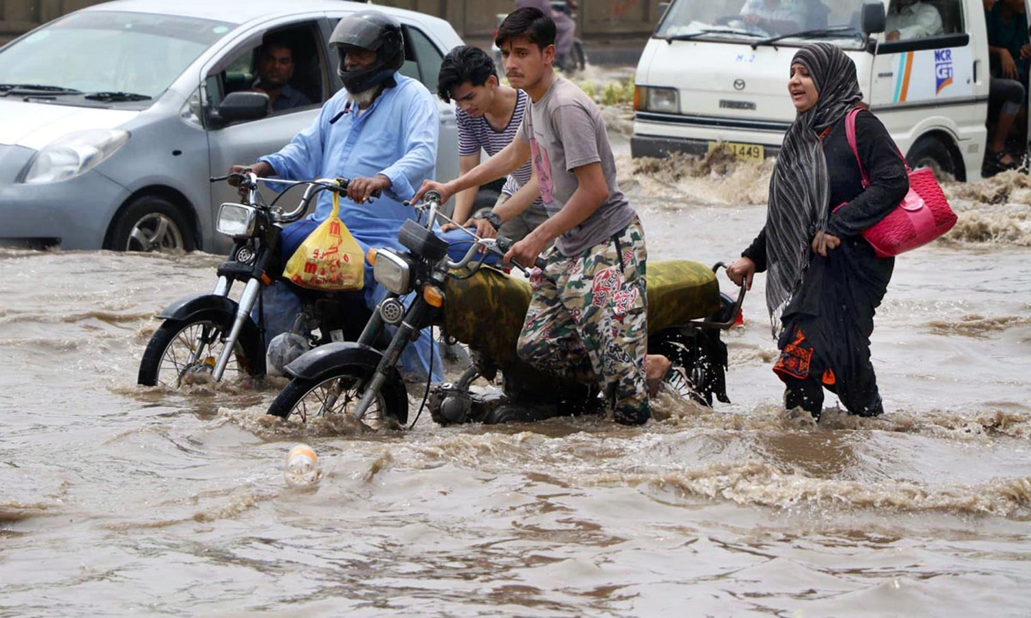 A motorcyclist pushes his bike through rainwater in Karachi's Ayesha Manzil area after first monsoon rain in the port city.— Online