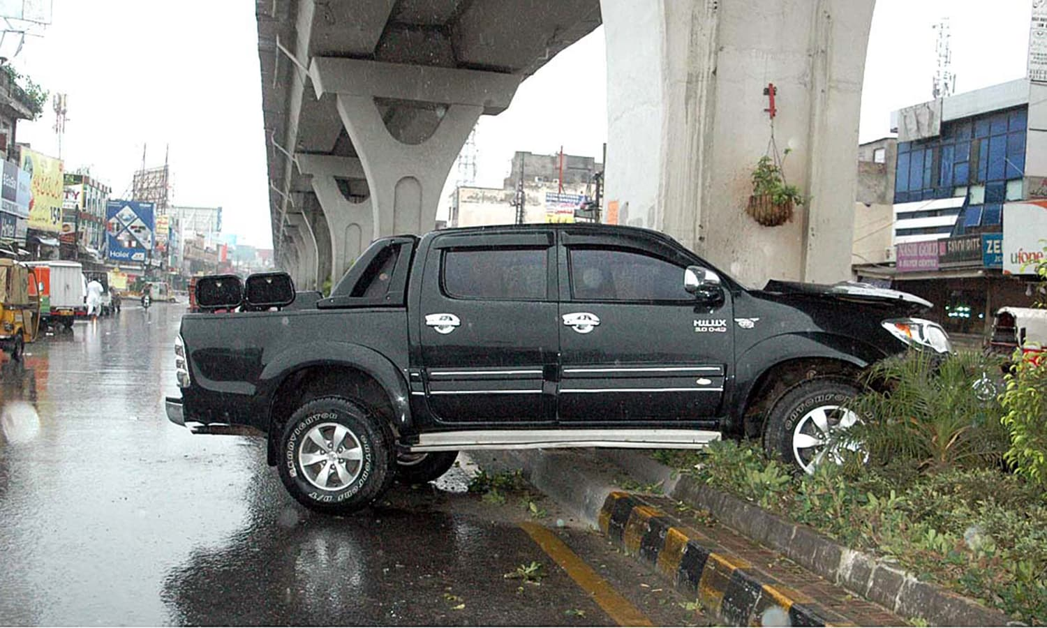 A view of a vehicle that ran over the greenbelt in Rawalpindi during the rain.— APP
