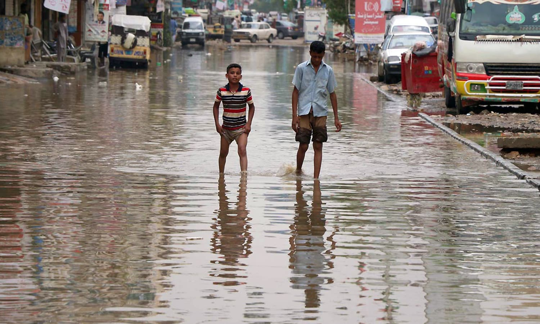 Boys walk through stagnant rainwater in Karachi's Mehmoodabad area.— Online