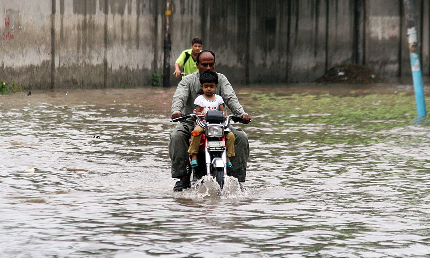 A motorcyclist passes through stagnant rain water in Lahore.— APP