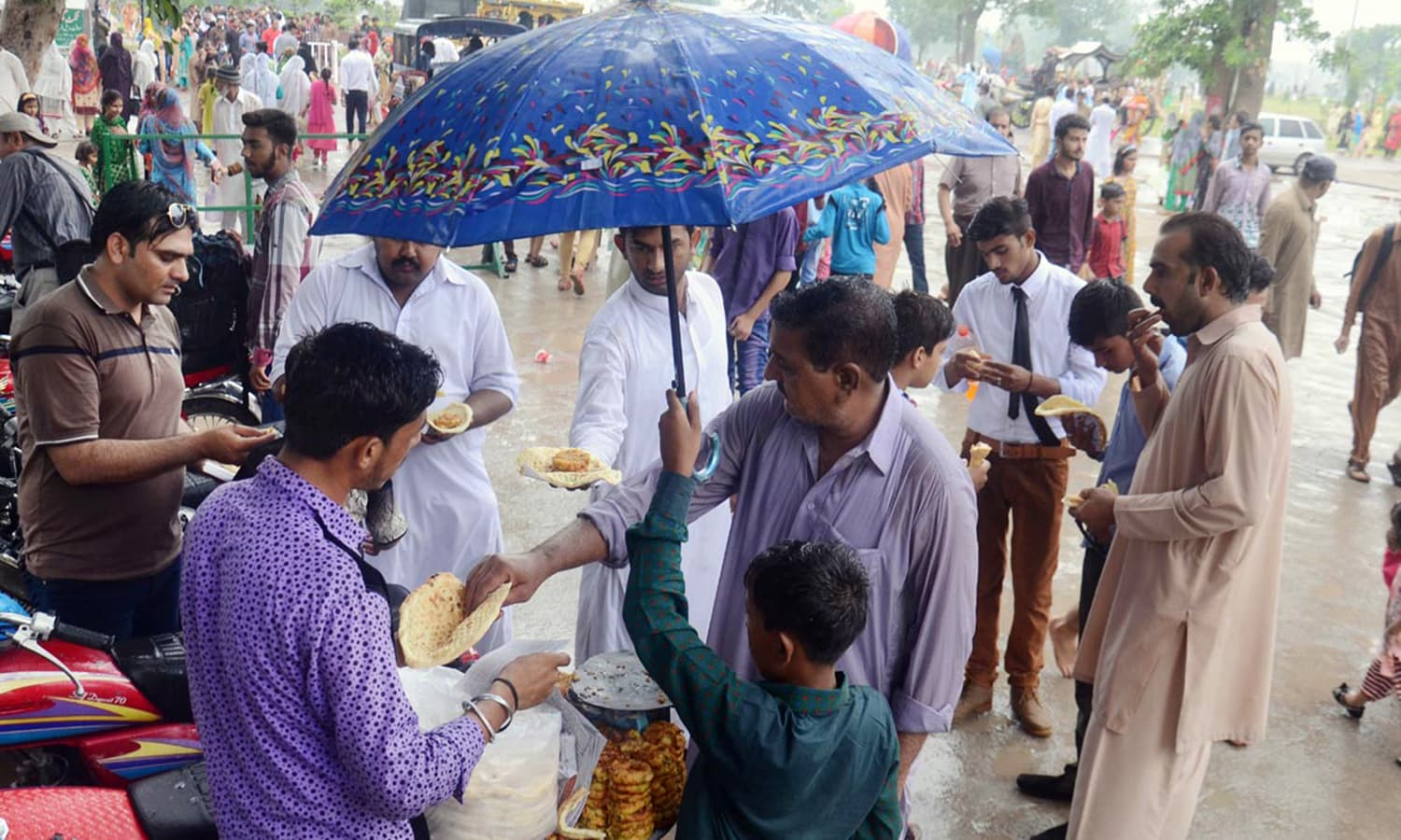People buy food items from vendors outside the Badshahi Mosque during light rain in Lahore.— Online