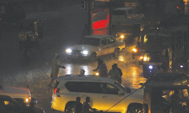 KARACHI: Commuters passing through Rashid Minhas Road during rain on Thursday night.—PPI