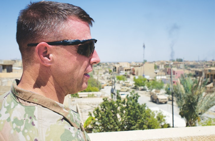 Colonel Pat Work of the US Army's 82nd airborne division looks at the skyline as he meets Iraqi commanders near the front lines on the rooftop of a house in Mosul.—AP