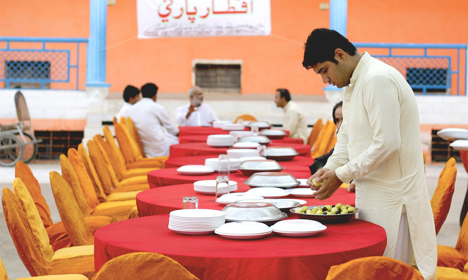 A young man lays the table for the guests for the evening's diverse Iftar party