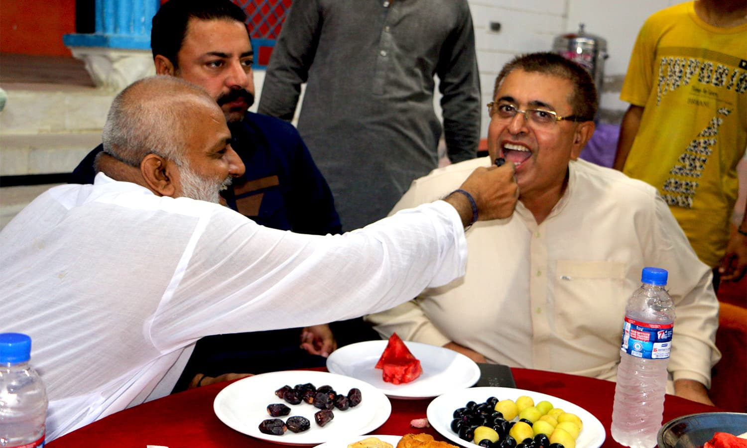Hindu religious leader Raju Baba feeding his Muslim compatriot after hearing the Azan.