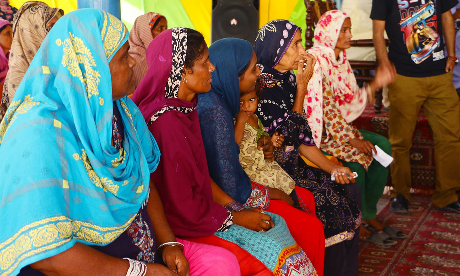 Women sat patiently as they waited for the distribution of Eid supplies.