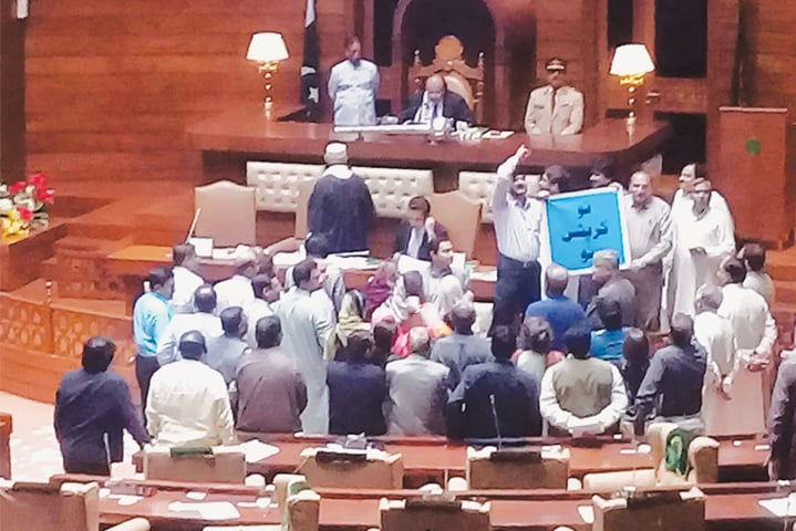 Members of the opposition in the Sindh Assembly hold a protest in front of Speaker Agha Siraj Durrani during Monday's stormy session.—PPI