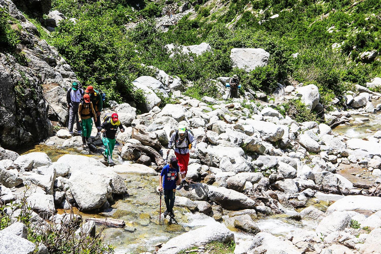 Tourists cross a small river on the way to Saidgai Lake.—Fazal Khaliq