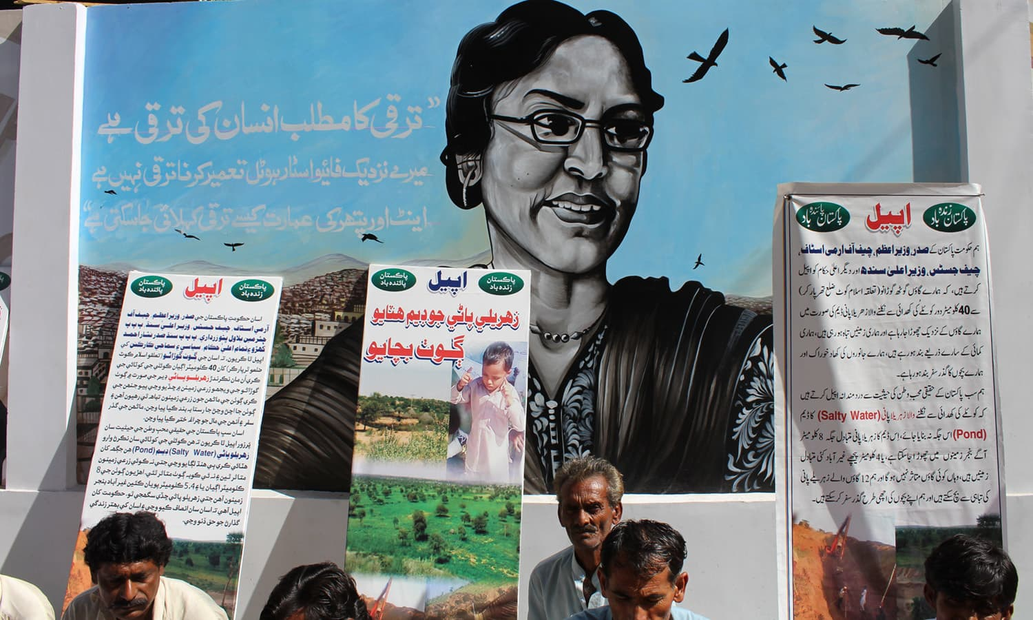 Protestors sit in front of a mural of Perween Rehman outside the Karachi Press Club.—Designed and implemented by Vasl Artists' Collective for 'I AM KARACHI Walls of Peace'