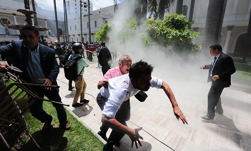 اپوزیشن ارکان حکومت کے حامیوں کے حملے کے بعد جان بچا کر بھاگ رہے ہیں—۔فوٹو/ اے پی