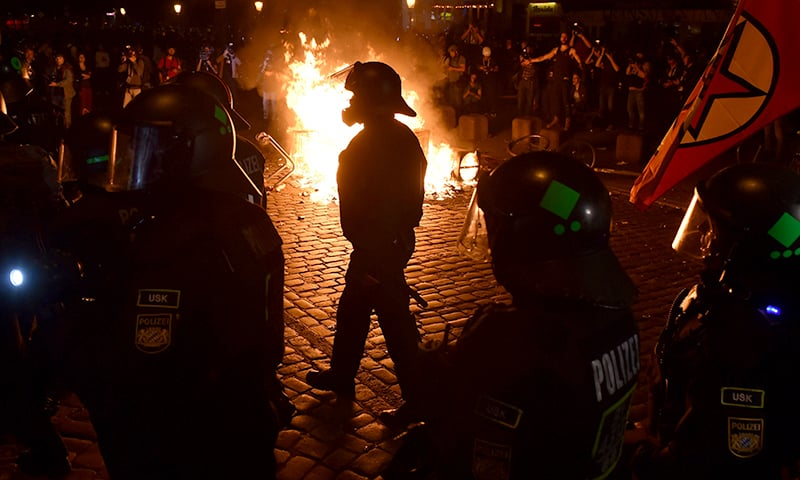 """Police officers walk in front of a fire started by protesters the """"Welcome to Hell"""" rally against the G20 summit in Hamburg. ─ AFP"""