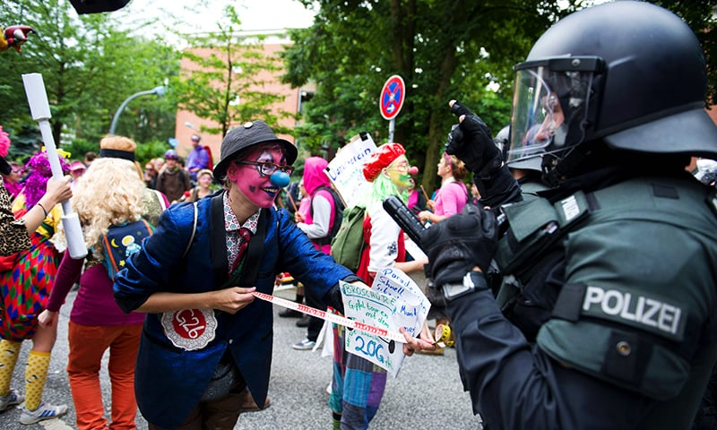 Demonstrators dressed as clowns face policemen as they take part in a protest titled '#BlockG20 - Color the Red Zone'. ─ AFP