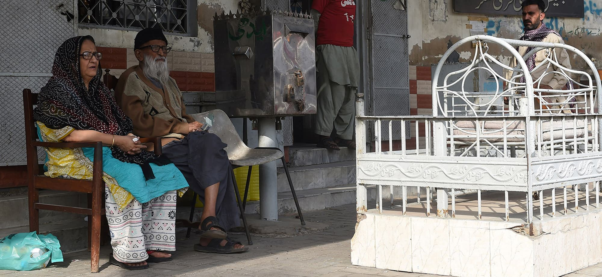 "In this photograph taken on February 15, 2016, Abdul Sattar Edhi (2nd L), the head of Edhi Foundation, sits with his wife Bilquis Edhi outside his office in the port city of Karachi.  He created a charitable empire out of nothing, masterminding Pakistan's largest welfare organisation. Today Abdul Sattar Edhi is revered by many as a national hero. / AFP PHOTO / ASIF HASSAN / To go with "" Pakistan-Social-Health' FEATURE by Caroline Nelly Perrot — AFP or licensors"