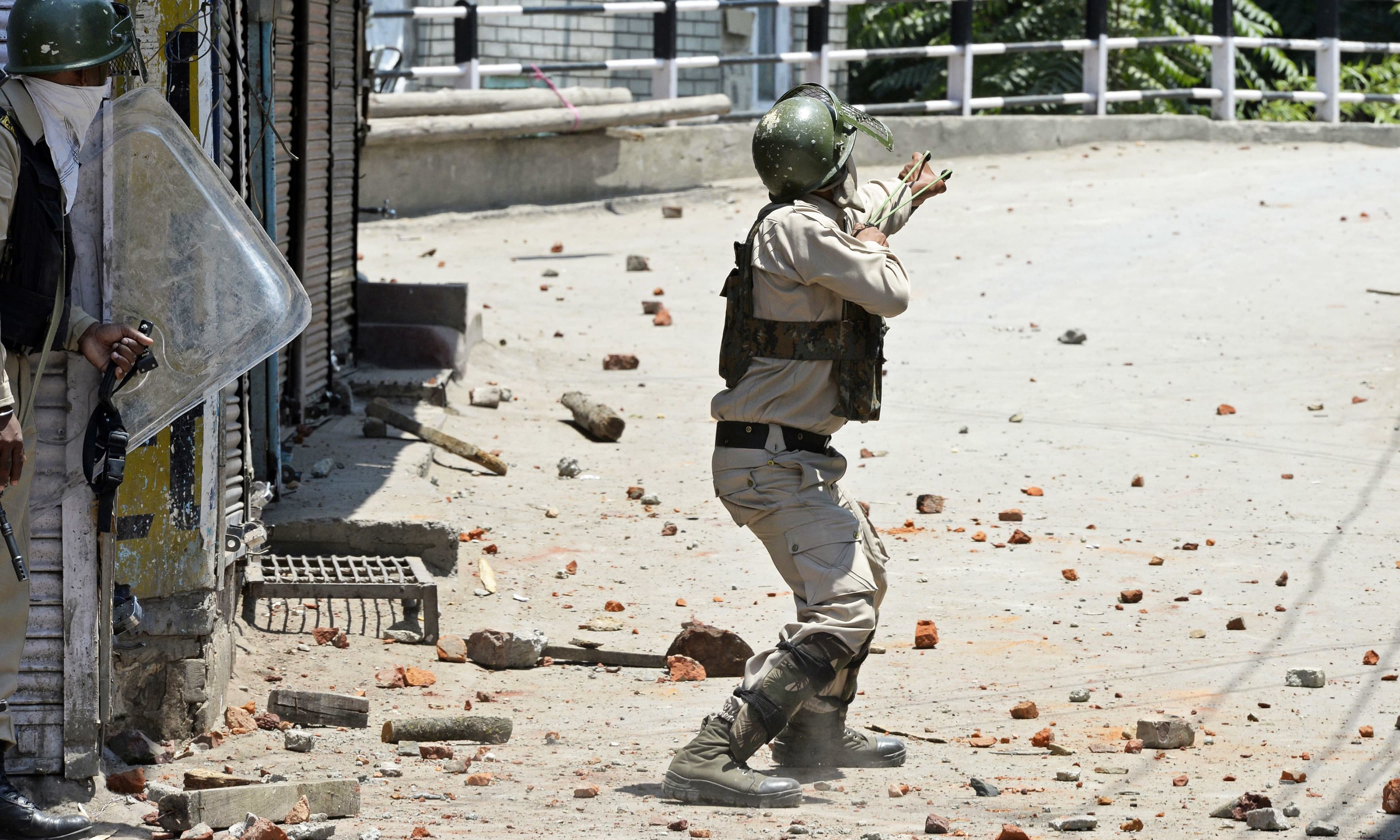 A paramilitary trooper uses a sling shot towards Kashmiri protesters in Srinagar. —AFP