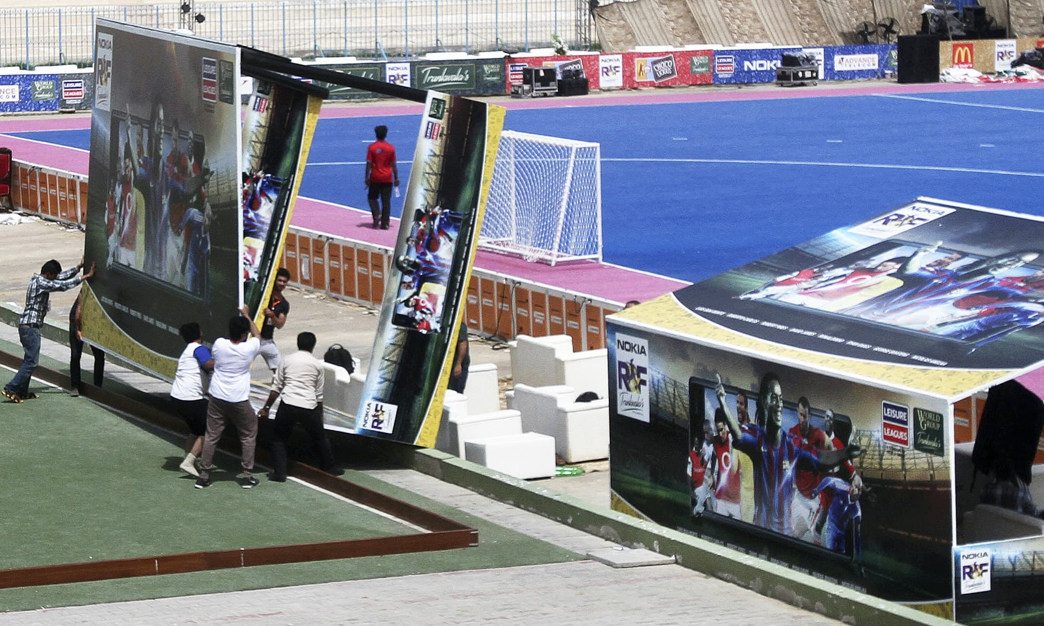 Workers install advertising boards at stadium. —AP