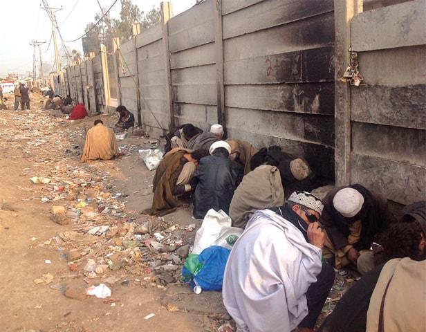 Addicts take drugs alongside a wall near Karkhano Market, Peshawar. — Dawn