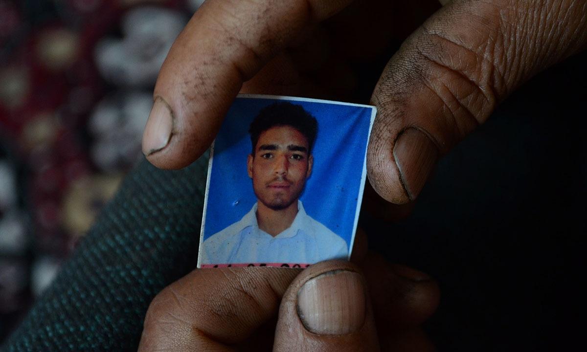 Saara Baano holds a photograph of her slain son Jalaluddin Ganai at their home in Tahab village