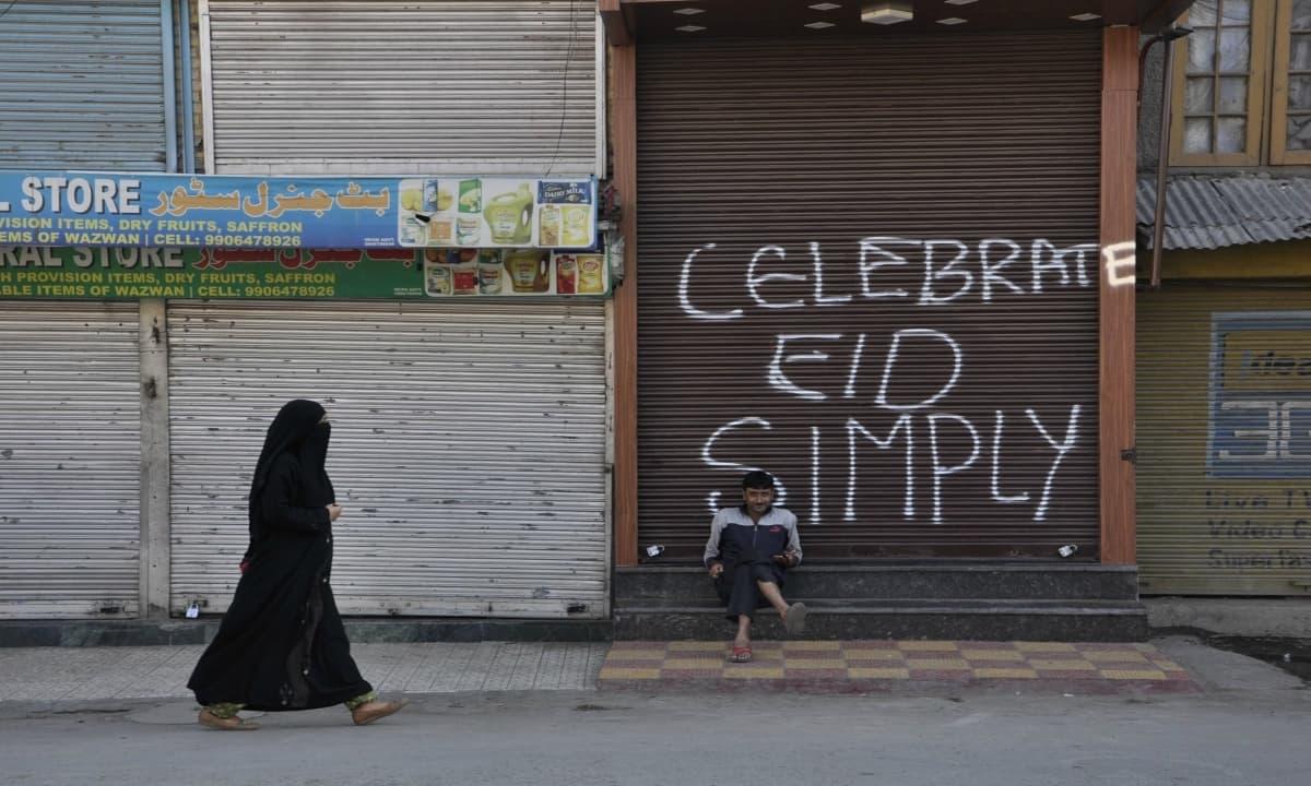 A woman walks past closed shops in Srinagar on the eve of Eid Al Adha on September 12, 2016