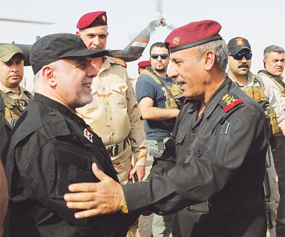IRAQI Prime Minister Haider al-Abadi (left) is all smiles as he meets a military officer in Mosul on Sunday.—AFP
