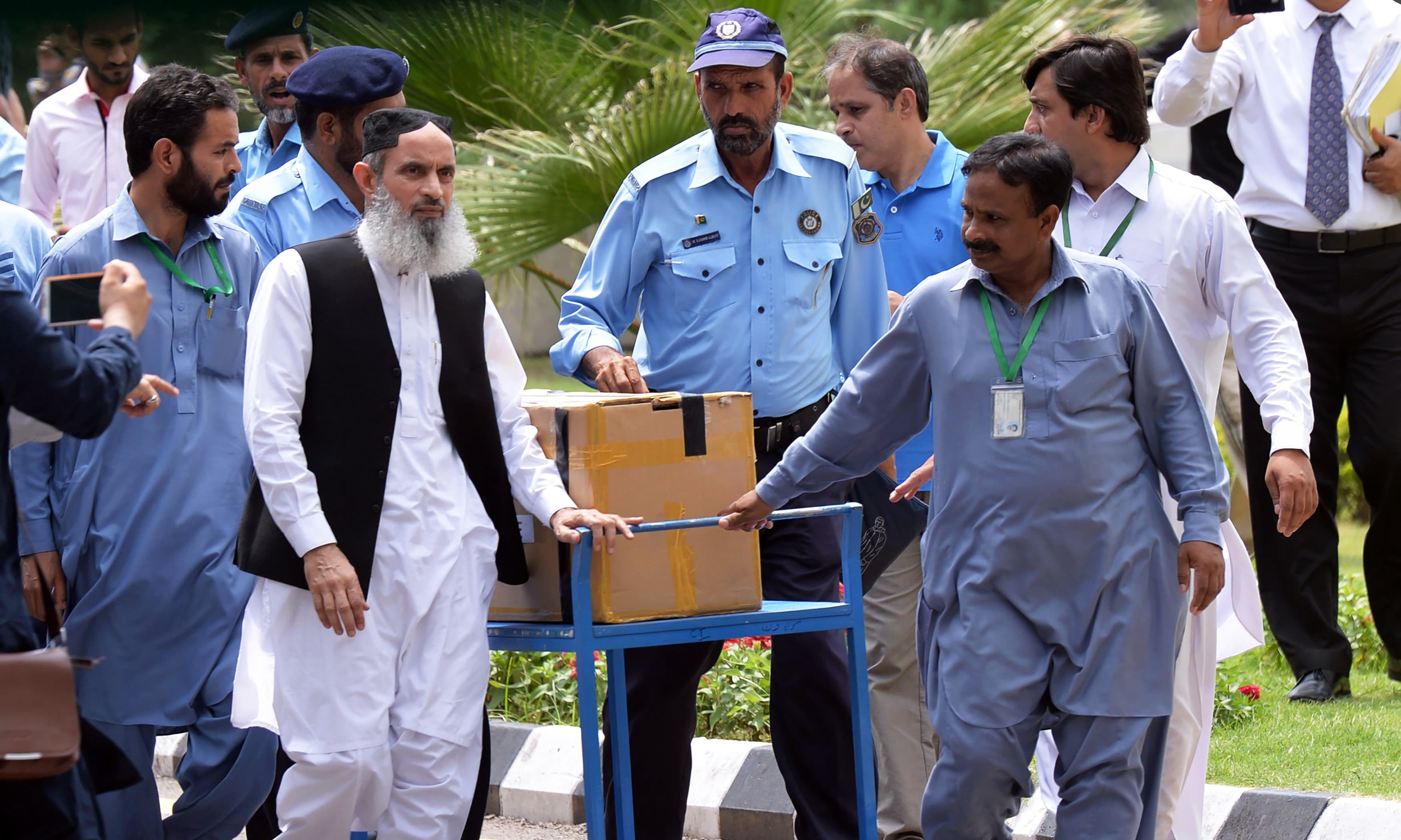 Officials transport a box of final evidence presented by the JIT. —AFP