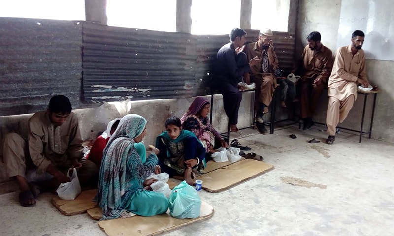 Families from Azad Jammu and Kashmir take shelter in a state-run school in Abbaspur city on Monday after fleeing their village along the LoC because of cross-border shelling by Indian troops.— AFP