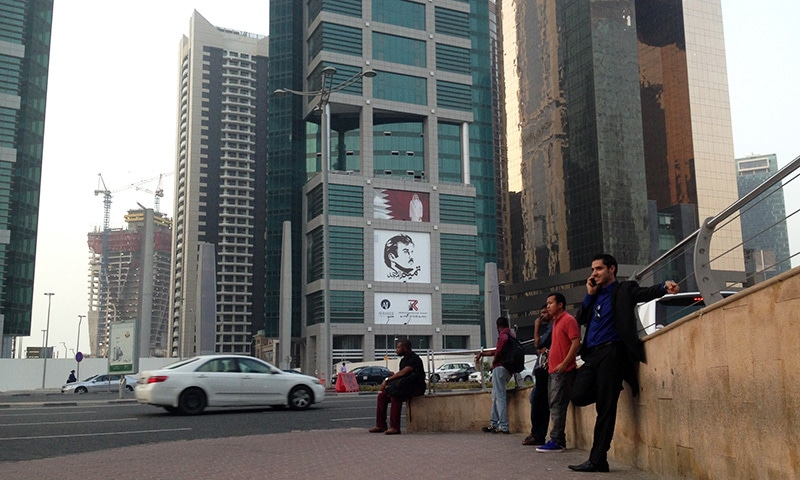 In this Sunday, July 9 file photo, men wait for a bus in front of a building with the poster of Qatari Emir Sheikh Tamim bin Hamad Al Thani.— AP
