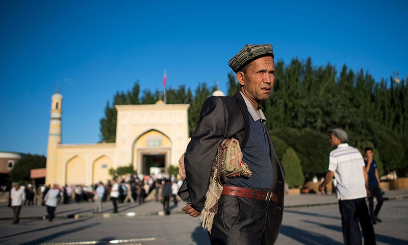 Картинки по запросу Police patrol as Uygur Muslims leave the Id Kah Mosque in Kashgar, Xinjiang after morning prayer. Photo: AFP