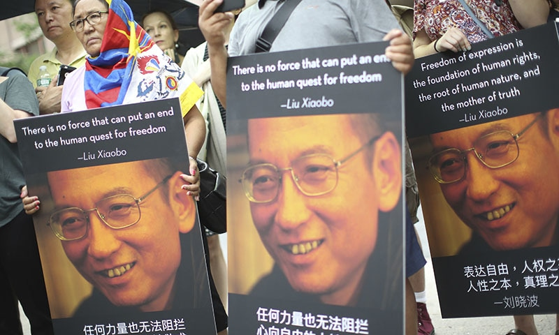 Participants hold photos of Liu Xiaobo during a vigil honoring Xiaobo's legacy and to protest continued human rights abuses in China─AP