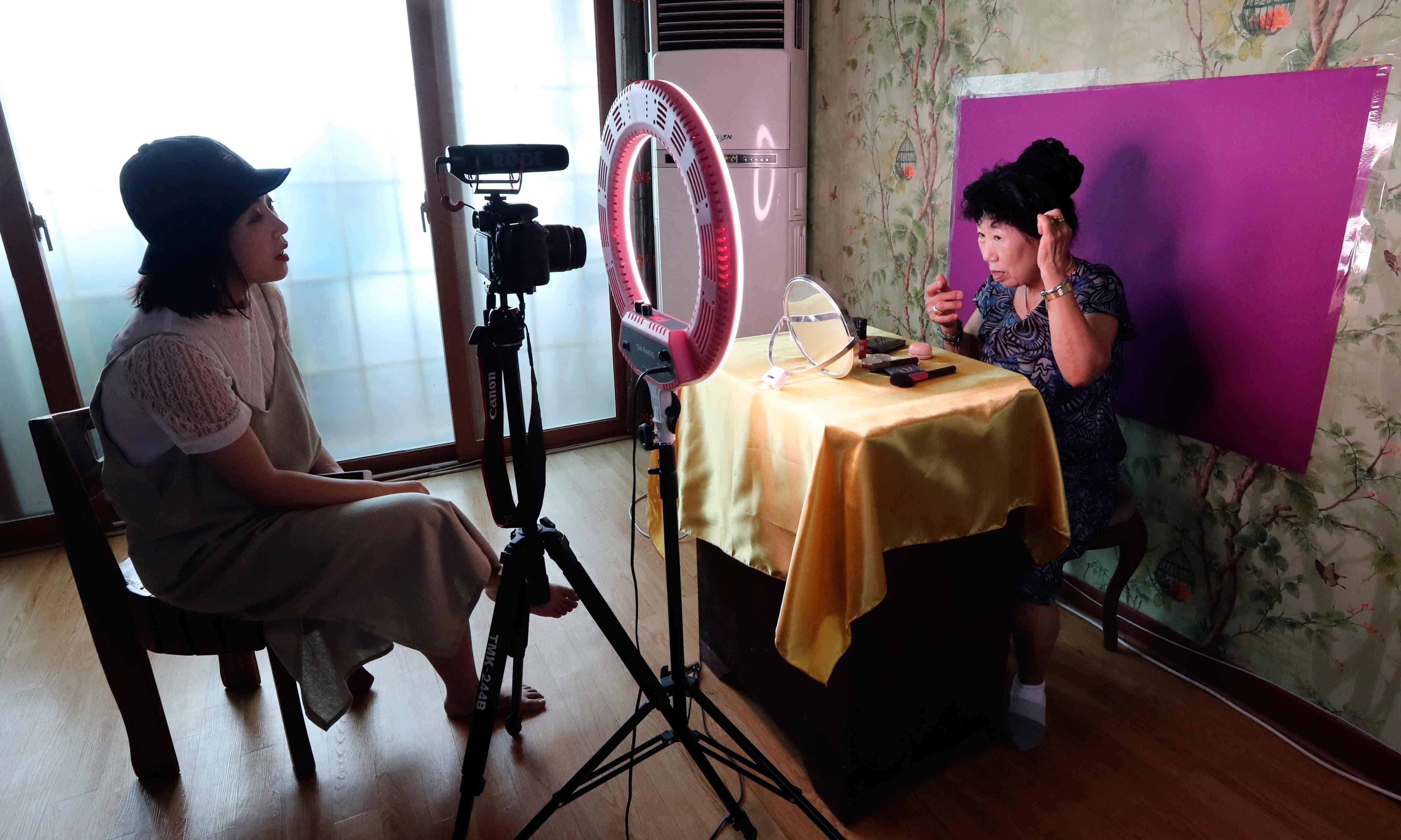خاتون اپنی پوتی کی مدد سے ویڈیوز ریکارڈ کرتی ہیں—فوٹو: اے پی