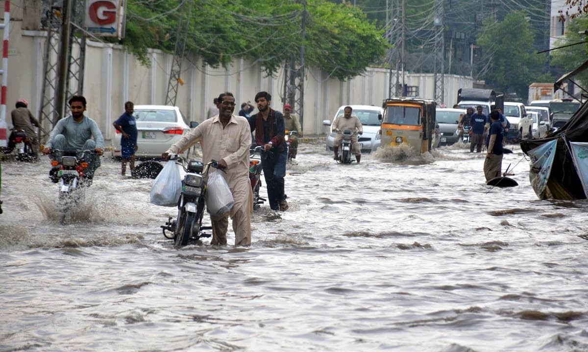 Motorists crossing the stagnant rainwater accumulated on road after heavy rain in Lahore. —Online